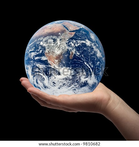 Female hand holding the earth. Black background.