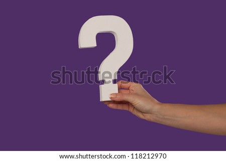 Female hand holding up a white question mark against a purple background conceptual of questions, query, why or what. - stock photo