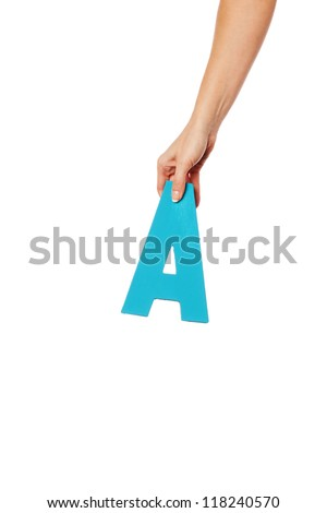 Female hand holding up the uppercase capital letter A isolated against a white background conceptual of the alphabet, writing, literature and typeface - stock photo