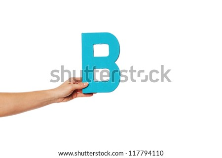 Female hand holding up the uppercase capital letter B isolated against a white background conceptual of the alphabet, writing, literature and typeface - stock photo
