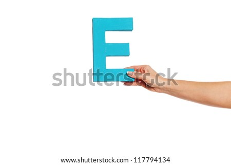 Female hand holding up the uppercase capital letter E isolated against a white background conceptual of the alphabet, writing, literature and typeface - stock photo