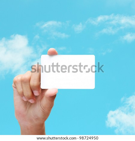 female hand holding white card on blue sky. - stock photo