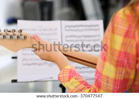 Female hand holding wooden neck of electric guitar and playing song using note papers in music stand closeup. Learning musical instrument, music shop or school, having fun enjoying hobby concept