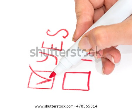 Female hand holds a marker and make a choice between yes and no