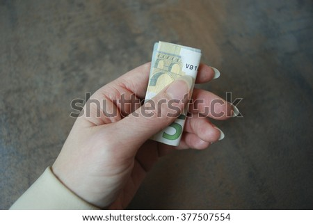 Female hand holds folded currency note (five euro).