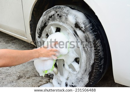 female hand is cleaning car tire with sponge; selective focus at hand - stock photo