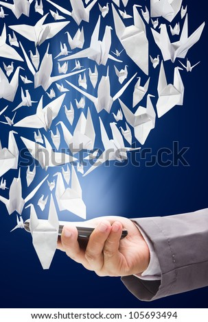 female hand is holding a modern touch screen phone With Origami Birds in flight. - stock photo