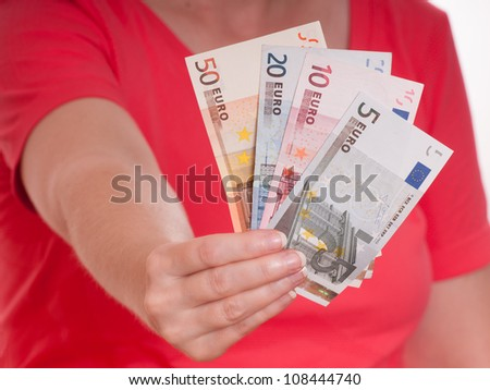 Female hand is holding some euro notes as fan into the front - stock photo