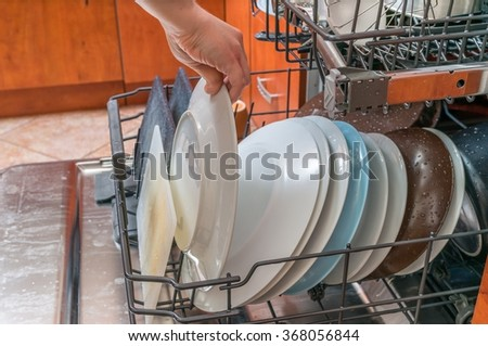 Female hand is putting dirty plate in dishwasher. - stock photo