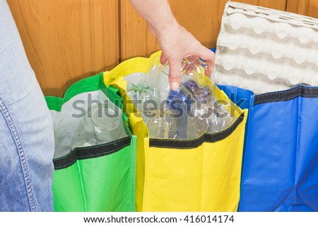 Female hand is sorting plastic to the yellow bag. Household Waste concept. - stock photo
