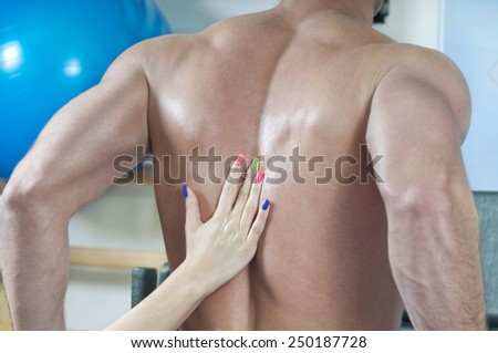 Female hand lubricates the male backs. - stock photo