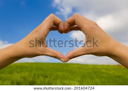 Female hand making a heart shape against a beautiful blue sky - stock photo