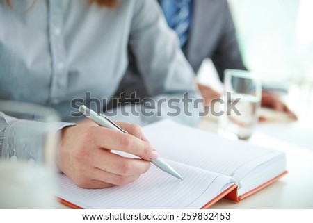 Female hand making notes in notepad