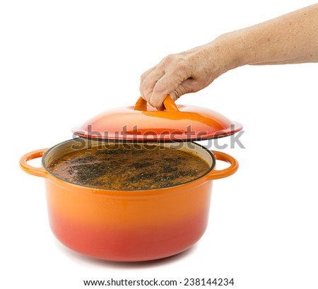 Female hand opens lid of lentil soup in cast iron cooking pot isolated on white background.    - stock photo