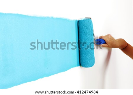 Female hand painting wall with paint roller - stock photo