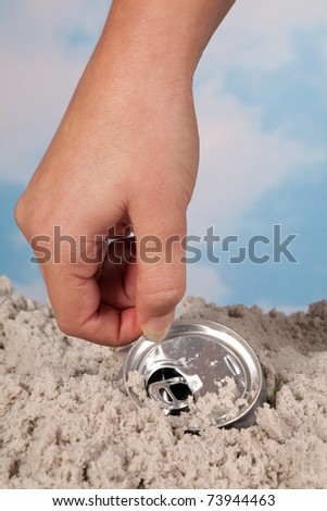 Female hand picking up a discarded soda can on a beach - stock photo