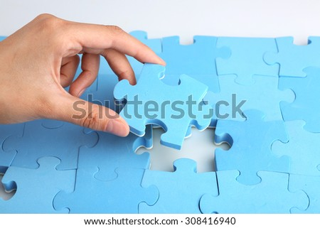 Female hand placing last piece of puzzle, closeup - stock photo