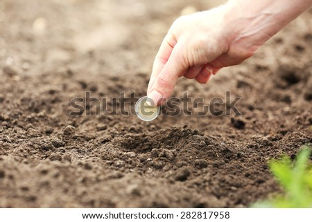 Female hand planting coin into soil, outdoors
