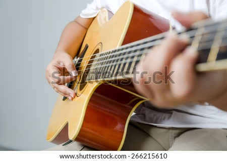 Female hand playing music by acoustic guitar - Close up shot and soft focus