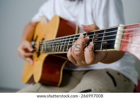 Female hand playing music by acoustic guitar - Close up shot focus on left hand and soft focus - stock photo