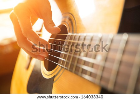 Female hand playing on acoustic guitar. Close-up. - stock photo