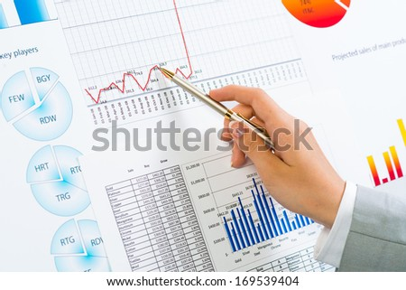 female hand pointing pen on financial charts, paper work in the office - stock photo