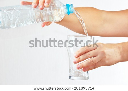 Female hand pour water into a glass from bottle on white background - stock photo