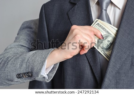 Female hand pulls money from the men of the jacket