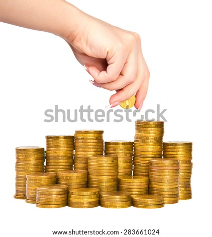 female hand puts a coin in a stack, isolated on a white background