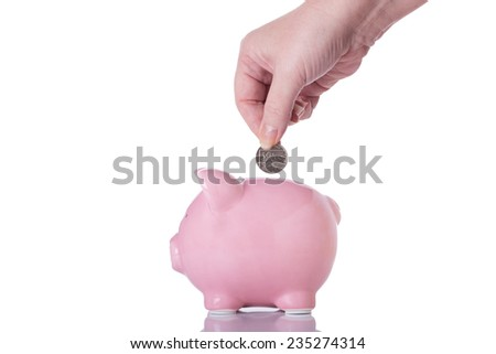 Female Hand Putting a Coin into a Piggy Bank Isolated on a White Background.  - stock photo