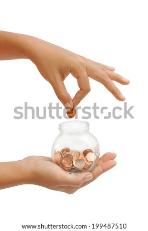 female hand putting a coin into glass bottle, concept saving for retirement - stock photo
