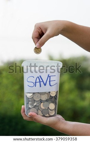 Female hand putting coin into jar - stock photo