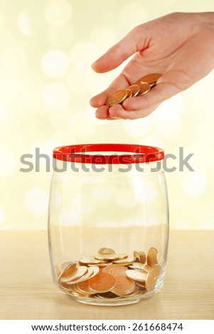 Female hand putting coins in glass bottle on bright blurred background - stock photo