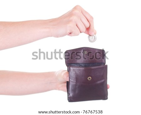 Female hand putting Polish Zloty coin into purse - stock photo