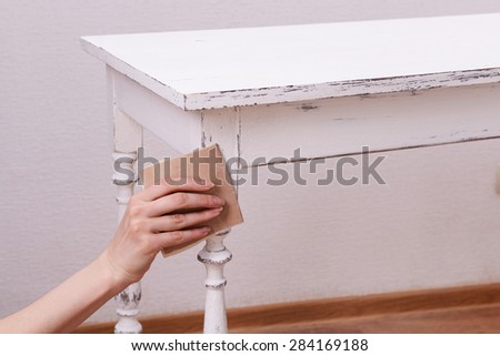 Female hand removing paint from wooden table for decoration, indoors - stock photo