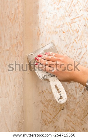 Female hand repairs wall with spackling paste - stock photo