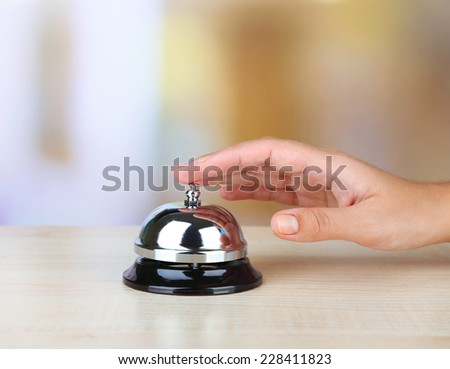 Female hand ring bell on  hotel reception desk, on bright background