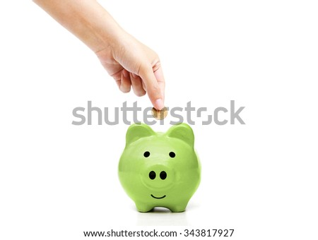 Female hand saving money in a green piggybank / Green saving concept