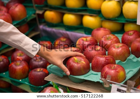 Female hand selecting red apple in supermarket, Japan