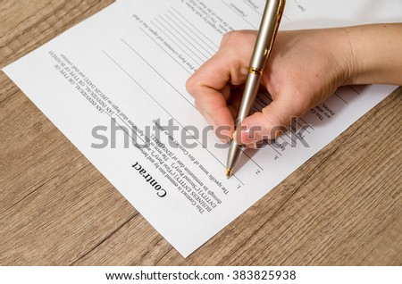 female hand signing a contract  on desk