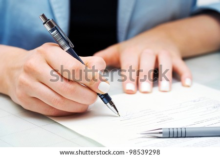 Female hand signing contract - stock photo