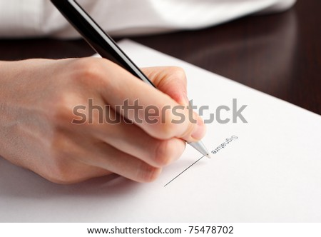 Female hand signing contract on the table. - stock photo