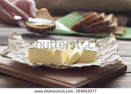 female hand smearing butter on fresh bread