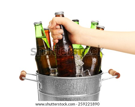 Female hand taking glass bottle of beer from metal bucket isolated on white - stock photo