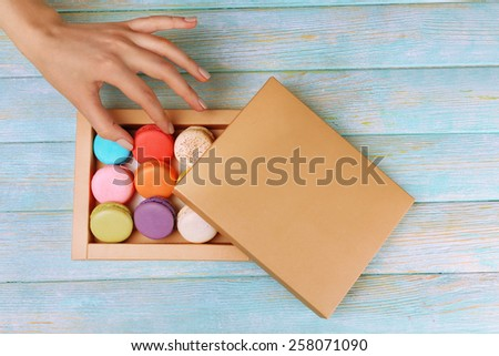 Female hand taking tasty colorful macaroons from box on color wooden background - stock photo