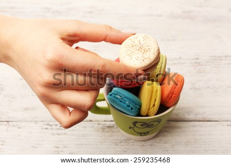 Female hand taking tasty colorful macaroons from cup on color wooden background - stock photo