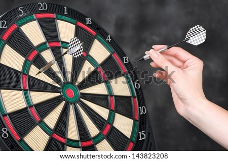 Female hand throwing darts at dartboard - stock photo