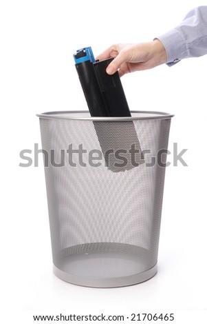 Female hand throwing used laser printer cartridge into metal trash bin over white - stock photo