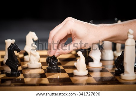 Female hand touching a pawn on the chessboard. - stock photo