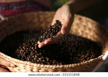 Female hand touching coffee beans in the basket - stock photo